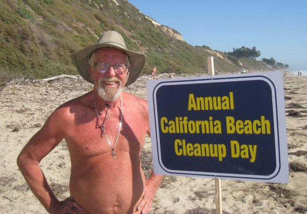 Man on beach with 'California Beach Cleanup Day' sign